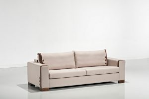A imagem mostra um espaço claro com paredes e piso branco, refletindo o sofá. No centro da imagem está o Sofá Accord, na cor branca com detalhes em marrom e pés em madeira.