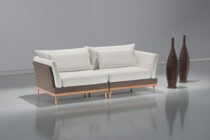 A imagem mostra um espaço claro com paredes e piso branco, refletindo o sofá. No centro encontra-se o Sofá Arezzo – Detalhe Fita, na cor branca com detalhes em Fita nos braços e encosto além dos pés em madeira. No lado direito do sofá estão dois vasos marrons.