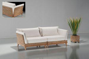 A imagem mostra um espaço com paredes e piso branco, refletindo o sofá. No centro da imagem encontra-se o Sofá Arezzo – Detalhe Junco, na cor branca. há detalhes em junco nos braços e encosto, seus pés são de madeira. Ao seu lado direito há um vaso bege. No canto superior esquerdo está uma pequena imagem mostrando o detalhe junco atrás do sofá.