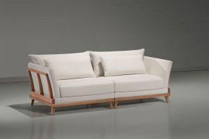 A imagem mostra um espaço com paredes cinza e o piso mais claro refletindo o sofá. Ao centro encontra-se o Sofá Arezzo – Detalhe Madeira, sua cor é branca, ele tem detalhes em madeira nos braços e pés também em madeira.