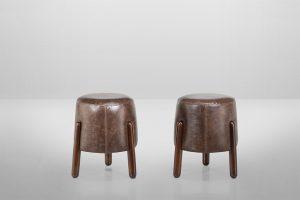 A imagem mostra dois puffs iguais, um ao lado do outro. Eles possuem a base redonda, em couro marrom e as pernas de madeira no mesmo tom. O fundo da imagem é cinza claro.