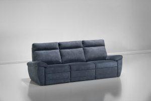 A imagem mostra um ambiente claro no qual há um sofá azul marinho de três lugares. Ele está posicionado na diagonal.