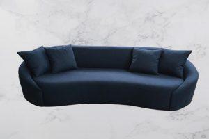 A imagem mostra um espaço com fundo mesclado com branco e cinza. No centro da imagem encontra-se o sofá Coral na cor azul marinho, ele tem quatro almofadas azul marinho.