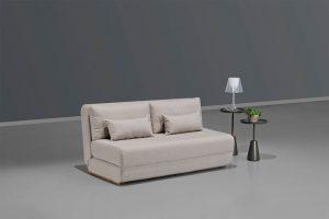 A imagem mostra um espaço com fundo cinza e piso branco. No centro encontra-se o sofá-cama loft com duas pequenas almofadas bege. Ao lado direito do móvel há duas mesas pretas detalhadas e, sobre ela, dois decorativos, um abajur branco e um vaso de flor amarelo.
