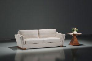 A imagem mostra um espaço com parede e piso cinza. No centro da imagem, abaixo de um foco de luz, encontra-se o sofá Onix, sua cor é branca e seus pés são de madeira. Ao lado há uma mesinha marrom e, sobre ela, está um vaso de flores branco.