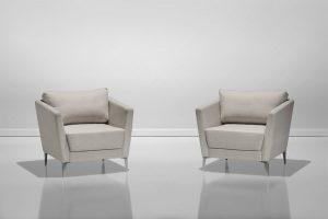 A imagem mostra um ambiente iluminado, com parede e chão na cor cinza claro, duas poltronas iguais. As poltronas são bege claro, possuem o encosto um pouco mais alto que os braços laterais e uma almofada encaixada. Os pés são de alumínio.
