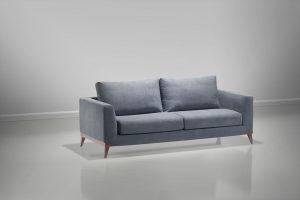 : A imagem mostra um espaço com parede e piso brancos. No centro da imagem encontra-se o sofá Kari, na cor azul claro, seus pés são de madeira.