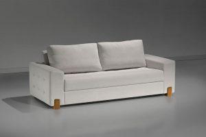 A imagem mostra um espaço escuro. Ao centro encontra-se o sofá Lazio, na cor branca, com alguns detalhes no estofado e pés em madeira.