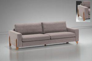 A imagem mostra um espaço com parede e piso brancos. Ao centro encontra-se o sofá Madrid, na cor cinza claro, seus pés são de madeira. No canto superior direito há uma pequena imagem mostrando o detalhe dos pés na lateral do sofá.