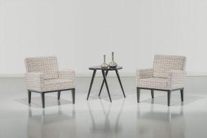 A imagem mostra um ambiente claro, com uma parede branca e chão cinza. No meio do ambiente há duas poltronas iguais e uma pequena mesa no meio delas. As poltronas são quadradas, com um tecido branco e detalhes em marrom, o encosto delas é mais alto que os braços. A pernas são de madeira e estão pintadas de preto. A mesa ao meio é de madeira e, sobre elas, há dois vasos decorativos prateados.
