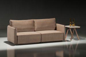 A imagem mostra um espaço escuro. No centro da imagem, abaixo de um foco de luz, encontra-se o sofá Nexus, na cor marrom. Ao seu lado direito, há uma mesinha com pés de madeira e parte superior cinza. Sobre ela estão algumas decorações marrons.