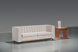 A imagem mostra um espaço com parede cinza e piso mais claro, refletindo o sofá. No centro da imagem encontra-se o sofá Prattice, na cor branca, com alguns detalhes no encosto e pés em madeira. Ao seu lado direito há uma mesinha marrom e, sobre ela, tem uma decoração na cor branca.