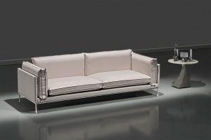 A imagem mostra um espaço escuro, com paredes na cor. No centro da imagem, abaixo de um foco de luz, encontra-se o sofá Win bege. Ao seu lado direito há uma mesinha cinza e, sobre ela estão três decorações.