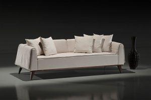 A imagem mostra um espaço escuro com parede cinza e o piso mais claro. No centro está o sofá Blend na cor branca. Sobre ele estão cinco almofadas, três na direita e duas na esquerda. À sua direita está um vaso preto.