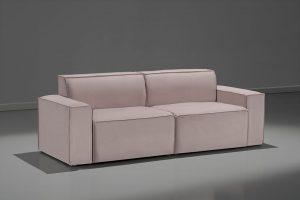 A imagem mostra um espaço escuro, com parede cinza e o piso mais claro, refletindo o sofá. No centro da imagem está o sofá Hermes, na cor marrom.
