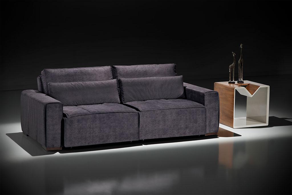 A imagem mostra um espaço preto. No centro da imagem, abaixo de um foco de luz, encontra-se o sofá Retrátil Jet na cor azul escuro. Do lado direito do sofá há uma mesinha marrom por fora e branca na parte interna. Sobre ela está uma decoração na cor preta.