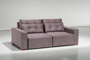 A imagem mostra um espaço com uma parede branca e um piso mais escuro que reflete o sofá. No centro da imagem encontra-se o sofá Retrátil Jhow na cor marrom e com detalhes em seu encosto.