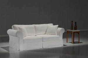 A imagem mostra um espaço com fundo cinza e piso branco. No centro encontra-se um sofá usando a Capa Liege na cor branca. Ao lado direito do móvel há uma mesa marrom e sobre ela estão dois decorativos na cor marrom.
