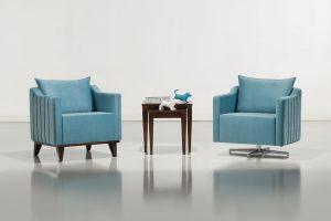 A imagem mostra duas poltronas, quase iguais, uma ao lado da outra com uma mesa entre elas. Elas são azuis, possuem um encosto baixo e os braços quase da mesma altura do encosto e há uma almofada apoiada nele. O que diferencia as duas poltronas são os pés, os da esquerda são de madeira e os da direita são de alumínio. A mesa no meio das poltronas é de madeira e possui duas estátuas no formato de cachorro e um livro. O fundo da imagem é um ambiente claro, com uma parede cinza e o chão um tom mais escuro.