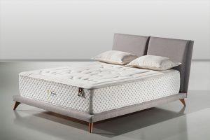 A imagem mostra uma cama com a base baixa e um colchão branco alto. A cabeceira e a base dela são estofadas na cor cinza e as pernas da cama são de madeira. Em cima do colchão, que está na cama, há dois travesseiros. O fundo da imagem é um ambiente com o chão e paredes em um tom claro de cinza.
