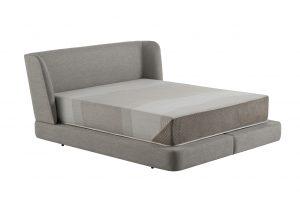A imagem mostra uma cama na diagonal. Tanto a cabeceira quando a base dela são estofadas, na cor cinza. A altura da base é alta e em cima dela há um colchão com listras em tons de cinza. O fundo da imagem é branco.