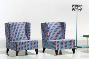 A imagem mostra duas poltronas iguais, uma ao lado da outra. Elas possuem encosto alto, não têm braços e o assento demonstra ser bem estofado. Os pés delas são de madeira, seu revestimento em tecido estampado xadrez, azul e laranja com fundo roxo. No canto direito da imagem há uma luminária e uma mesa de apoio. O fundo da imagem é em um ambiente com a parede e o chão cinza claro.