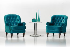 A imagem mostra duas poltronas iguais e uma mesa no meio delas. As poltronas são verdes, com o encosto arredondado, uma almofada alta encaixada no assento e os pés de madeira. A mesa que está no meio é branca e redonda. Em cima dela há duas garrafas decorativas e outro objeto arredondado, os três são verdes. O fundo da imagem é um ambiente claro, com a parede e o chão cinza claro.