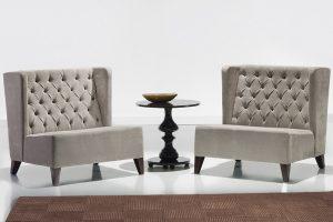 A imagem mostra duas poltronas iguais e uma mesa entre elas. As poltronas são em um tom cinza claro, tem um encosto alto, não possuem braços e o assento é bem estofado. As pernas são de madeira. A mesa que está no meio das poltronas também é de madeira, redonda e com detalhes na estrutura que a deixa de pé. Em cima dela há um objeto de decoração no formato de uma tigela. O chão e a parede do ambiente são brancos e há um tapete marrom no chão.