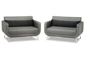 A imagem mostra duas poltronas iguais, em cor cinza, uma ao lado da outra. Elas possuem os pés em aço inox. As duas tem uma almofada decorativa preta sobre o assento. O fundo da imagem é branco.
