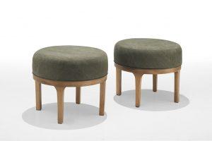 A imagem mostra dois puffs redondos, com a parte superior estofada na cor verde escuro, base e pernas de madeira. O puff do lado esquerdo está mais na frente e o do lado direito mais para trás. O fundo da imagem é cinza claro.