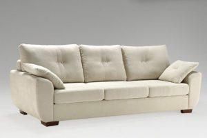 A imagem mostra um ambiente com fundo degradê branco e cinza. No centro encontra-se o Sofá Piaceri, na cor branca com pés de madeira nos cantos do sofá. Há pequenas almofadas, uma em cada canto do sofá.