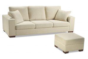 A imagem mostra um ambiente com fundo totalmente branco. No centro encontra-se o Sofá Spazio, na cor bege com pés de madeira nos cantos do sofá. Na frente está um puff quadrado com pés de madeira e nas mesmas cores do sofá.