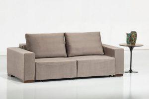 A imagem mostra um ambiente claro, com paredes brancas e um piso claro refletindo partes do sofá. No centro encontra-se o sofá na cor bege com quatro pés de madeira, um em cada canto do sofá. Sofá com encosto retrátil e duas almofadas. Na lateral direita do sofá tem uma mesa na cor marrom. Acima dela há dois enfeites detalhados lado-a-lado.
