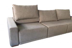 A imagem mostra um espaço com fundo totalmente branco. No centro da imagem encontra-se uma parte do sofá soft na cor marrom.
