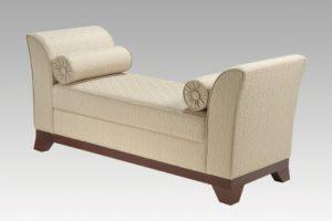 A imagem mostra o sofá Karol na cor bege com uma textura. Ele possui dois rolinhos decorativos próximo aos braços do sofá, um de cada lado. A parte inferior do sofá é de madeira, em um tom marrom escuro. O fundo da imagem é cinza claro.