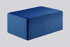 A imagem mostra um puff retangular na cor azul escuro com uma textura no tecido. O fundo da imagem é cinza.