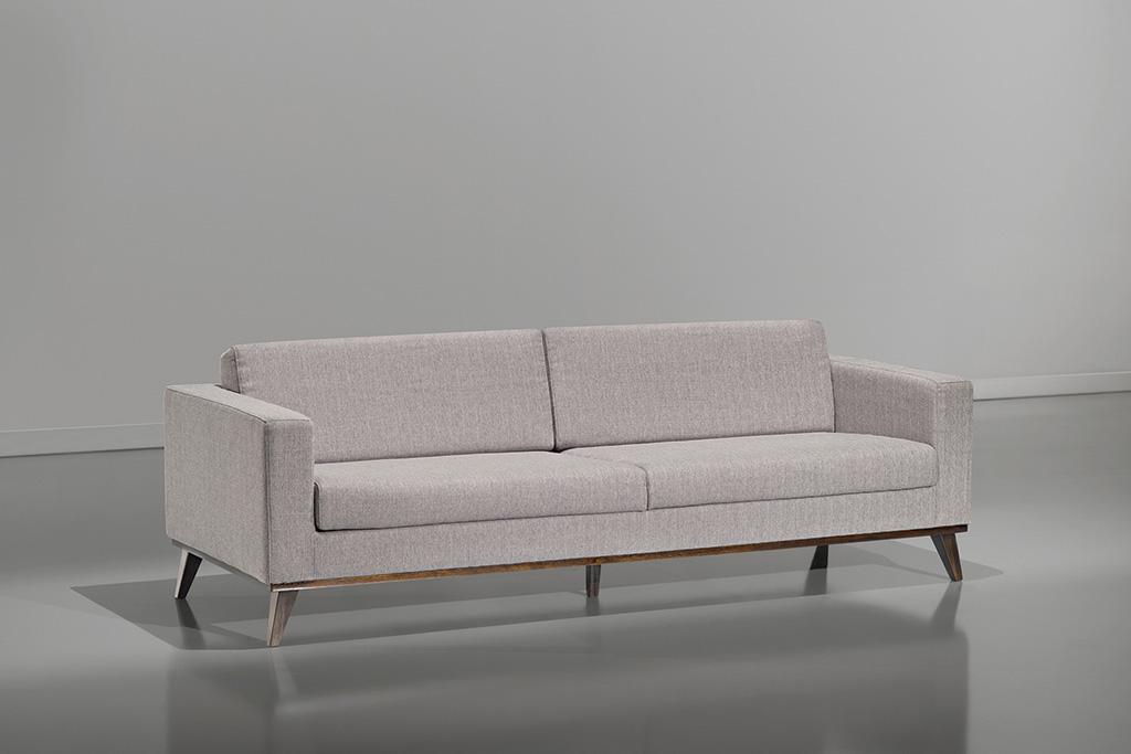 A imagem mostra um ambiente claro, com paredes brancas e piso refletindo partes do sofá. No centro da imagem encontra-se um sofá na cor branca com pés em madeira.