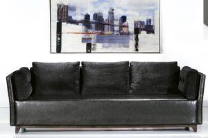 A imagem mostra um ambiente claro, com paredes brancas e piso refletindo partes do sofá. Na parede em cima do sofá encontrasse um quadro com a imagem da ponte de nova Iorque. No centro encontra-se um sofá na cor preta com cinco almofadas no encosto e nos braços do sofá. Pés em aço.