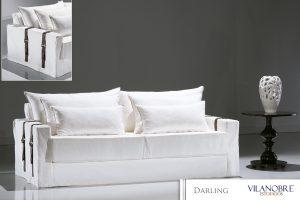 A imagem mostra um espaço com fundo cinza e piso branco mostrando um pouco o reflexo do sofá. No centro da imagem encontra-se um sofá usando a Capa Darling na cor branca com detalhes em marrom nos braços. Do lado direito do sofá encontra-se uma mesa marrom detalhada e em cima um vaso na cor branca. No canto superior esquerdo há uma imagem destacando o detalhe marrom nos braços do sofá.