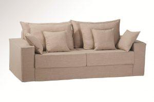 A imagem tem um fundo degradê branco e cinza. No centro encontra-se um sofá usando a Capa Lucia na cor marrom.