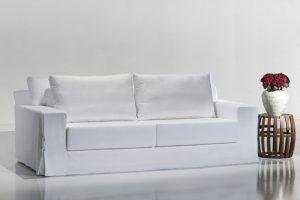 A imagem mostra um ambiente claro e no centro está o sofá usando a Capa Madras na cor branca. À direita há uma mesinha em formato de barril na cor marrom. Em cima dela tem um vaso branco com flores vermelhas.