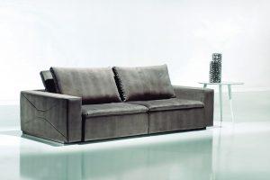 A imagem mostra um ambiente com paredes claras, o chão branco reflete o sofá. No centro da imagem encontra-se o Sofá Retrátil Galles na cor cinza. Ao lado direito há uma mesinha branca com três pilares, em cima dela há decorações na cor cinza.