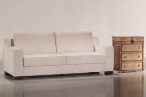 A imagem mostra um ambiente claro, com paredes brancas e um piso claro refletindo partes do sofá. No centro encontra-se o sofá na cor branca com quatro pés de madeira, um em cada canto do sofá. Na lateral direita do sofá encontra-se um móvel de madeira com três gavetas.