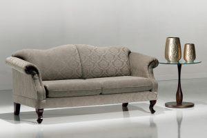A imagem mostra um ambiente claro, com paredes brancas e um piso claro refletindo partes do sofá. No centro encontra-se um sofá, na cor cinza, com detalhes no estofado. Seus encostos são refinados e os braços são curvados para o lado de fora. Seus pés são de madeira escura e curvada. Na lateral direita do sofá encontra-se uma mesa com seu pé detalhado em madeira escura e o tampo de vidro. Em cima dela encontram-se dois vasos um maior que o outro, lado-a-lado, na cor cinza com detalhes.