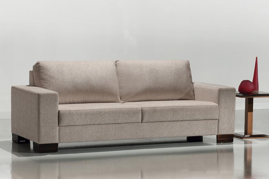 A imagem mostra um ambiente claro, com paredes brancas e um piso claro refletindo o sofá. No centro encontra-se o sofá na cor bege com quatro pés de madeira, um em cada canto do sofá. Sofá com encosto retrátil onde possui duas almofadas grandes para melhor conforto. Na lateral direita do sofá tem uma mesa na cor marrom, com um pilar e uma mesa redonda em cima. Há também dois enfeites vermelhos em cima da mesa um redondo e um triangular.