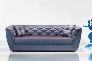 A imagem mostra um ambiente claro, com parede branca e piso branco. No centro encontra-se um sofá na cor azul com detalhes no estofado e dois travesseiros um em cada canto do sofá também nas cores azuis. Na lateral direita do sofá temos a metade de uma mesinha azul.
